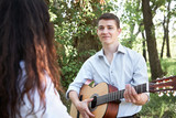 young couple walking in the forest, playing guitar and dancing, summer nature, bright sunlight, shadows and green leaves, romantic feelings - 220908483