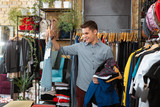 Nice sale. Cheerful handsome young man looking at the pair of shorts and enjoying amazing sales in clothes shop - 220908499