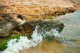beautiful sea landscape, closeup of stone on the beach, sea coast with high hills, wild nature - 220908695