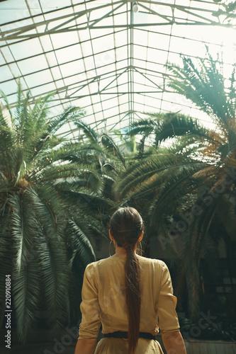 Widok z tyłu sprawny egzotyczny kobieta oglądania palmy w tropikalnym gar