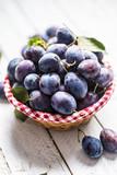 Sweet ripe plums in basket on garden table - 220917609