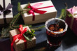 christmas spirit and holidays festivity. assortment of presents in gift boxes on black background. hot and spicy mulled wine in a glass.