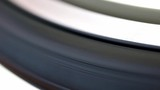 Detail of rotating tire from road bike. A black tire ride on white background, close up view. - 220920420