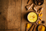 Hot turmeric milk with spices on wooden table - 220923613