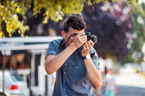 Fototapeta Young professional male photographer using camera at street