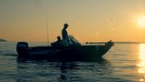Sunrise landscape with two men equipped for fishing sailing across open water - 220930408