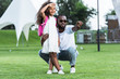 african american father pointing on something to daughter with school bag in park