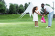 african american daughter giving school bag to father in park