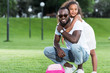 african american daughter hugging father from back in park, pink bag on grass