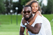 african american daughter hugging smiling father from back in park
