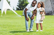 african american father and daughter holding hands in park and looking away