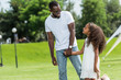 african american father and daughter holding hands and looking at each other in park