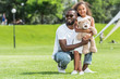 smiling african american father squatting and hugging daughter with teddy bear in park