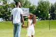 rear view of african american police officer and daughter holding hands and walking in amusement park