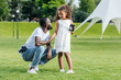 african american daughter holding father police badge in park