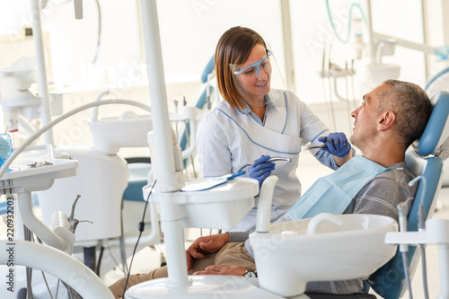 Dentist  in dental office talking with male patient and preparing for treatment.