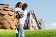 african american father holding adorable daughter on green hill at amusement park