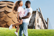 side view of african american father holding daughter on green hill at amusement park