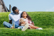 african american father and smiling daughter sitting on hill with soda and teddy bear at amusement park