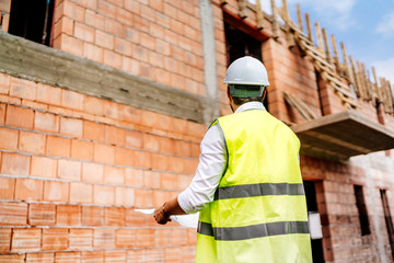 Construction engineer on construction site background, man wearing safety vest, hard top on construction site