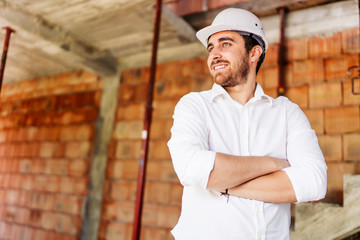 confident architect visiting the construction site. Portrait of construction worker with brick walls