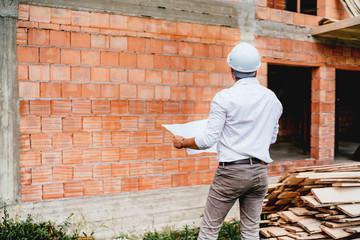 construction engineer with plans, working on building construction site. brick walls, infrastructure on construction site