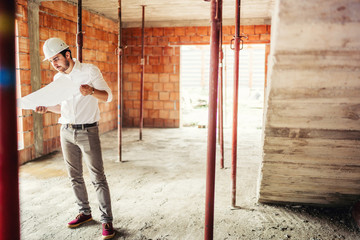 male engineer working on construction site, inside interior brick walls wearing hard hat and reading plans