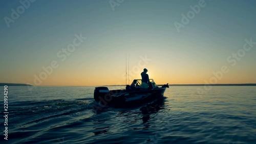 Fishermen are sailing across water during sunrise