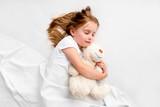 Girl hugging teddy bear laying on bed - 220936260