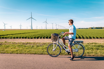 young man with bycicle looking at the huge winmills in the Netherlands, windmill park farm at the Noordoospolder Flevoland Netherlands, man bike