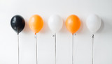 holidays, decoration and party concept - orange, black and white air balloons for halloween or birthday on white background - 220940087