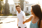 Loving couple walking outdoors while holding hands of each other. - 220941092