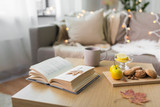 hygge and cozy home concept - book, autumn leaves, cup of tea with lemon, almond nuts and oatmeal cookies on table - 220941272