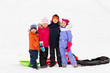 childhood, friendship and season concept - group of happy little kids with sleds hugging in winter