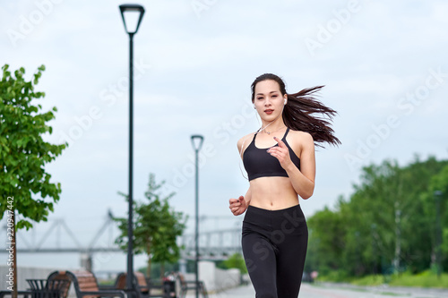 Fototapeta Running asian woman on the waterfront. Morning jogging. The athlete trains