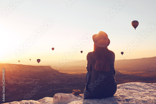 Foto Murales View from the back of a girl in a hat sits on a hill and looks at air balloons in Cappadocia in Turkey.