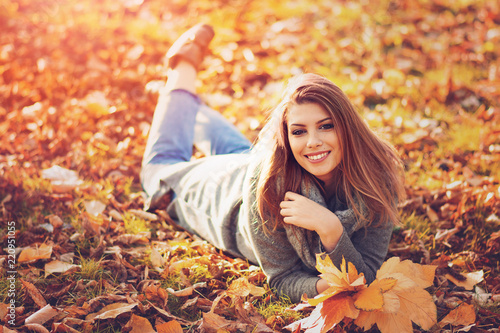 Leinwandbild Motiv Young woman lying in leaves in park on sunny autumn day. Natural lighting, filter applied.