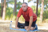 Middle aged man exercising on mat outdoors - 220951874