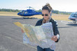 young woman helicopter pilot reading map