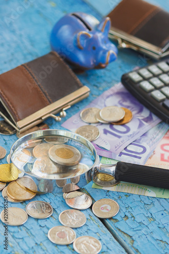 Canadian dollars, coins, magnifuing glass and calculator on the wooden background - 220955258