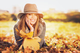 Gorgeous young woman in autumn in park with big yellow leaves, smiling and enjoying nature. Natural lighting, retouched, back light, closeup,  copy space. - 220955416