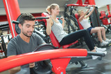 young athletic adults in sportswear training in gym - 220956244
