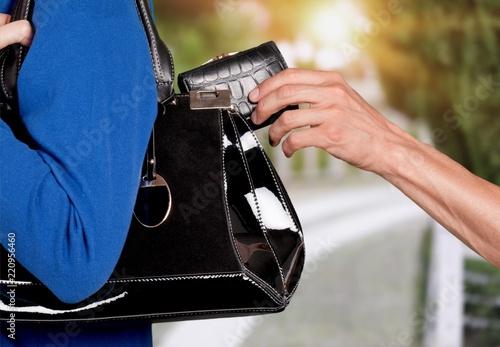 Przycięte zdjęcie złodzieja kradnącego portfel z damskiej torebki
