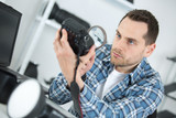 Man looking at camera body with magnifying glass - 220958220