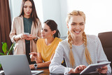 smiling businesswoman with digital tablet and her colleagues behind at modern office