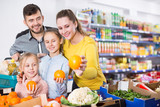 Family shopping together in greengrocery store choosing oranges