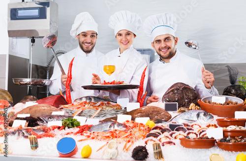 Leinwanddruck Bild Chefs offering seafood in restaurant