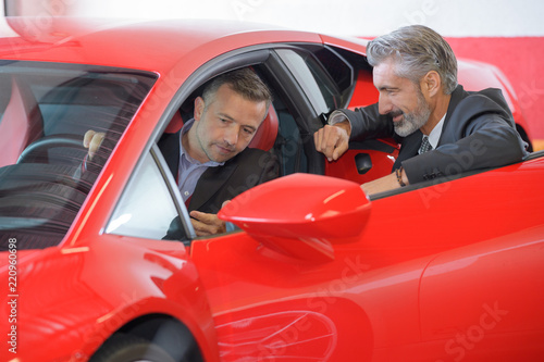 man in a red car in showroom - 220960698