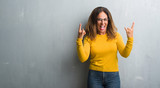 Middle age hispanic woman over grey wall wearing glasses shouting with crazy expression doing rock symbol with hands up. Music star. Heavy concept.