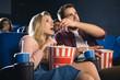 Leinwanddruck Bild - emotional couple with popcorn watching film together in cinema